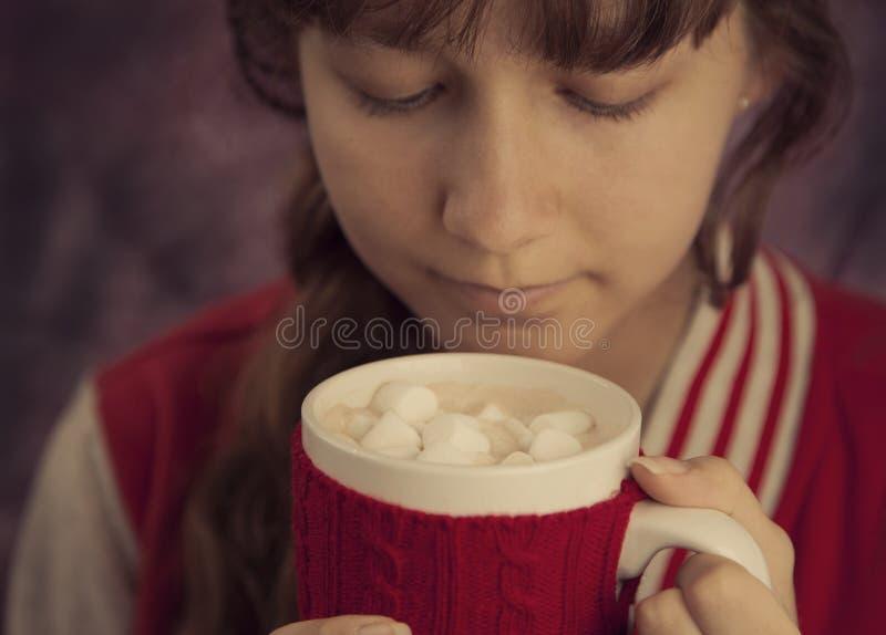 Junges Mädchen, das Schale heiße Schokolade mit Eibischen hält stockfotos