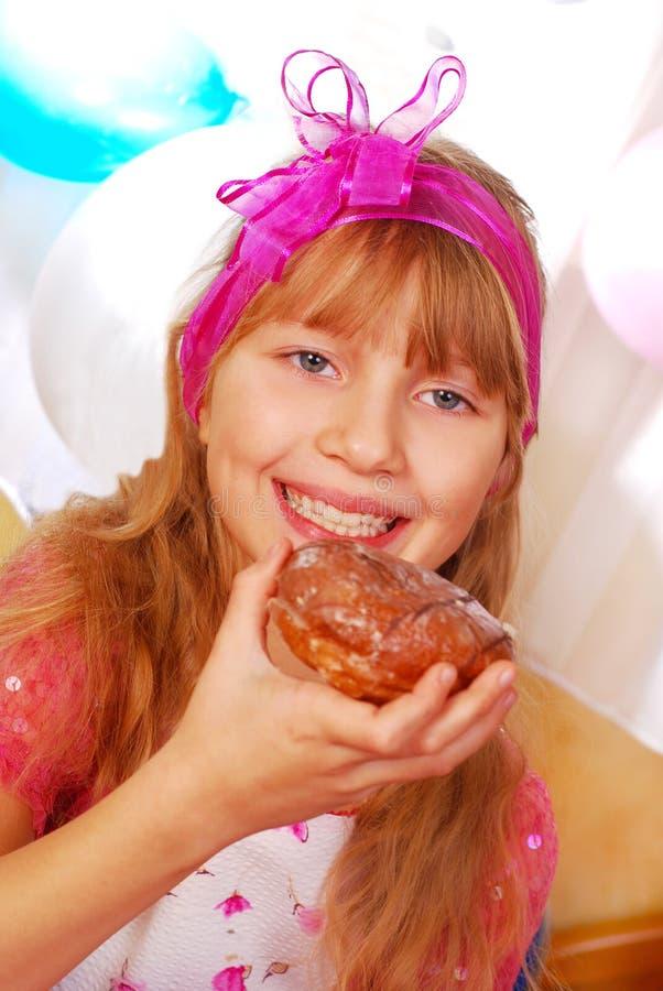 Junges Mädchen, das Schaumgummiringe auf Party isst stockfotos