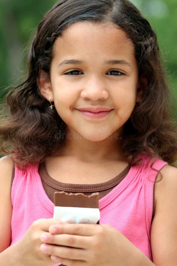 Junges Mädchen, das Schokolade isst stockfotos