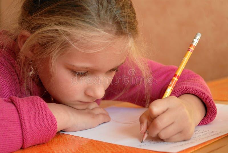 Junges Mädchen, das Schulearbeit erledigt stockfotografie