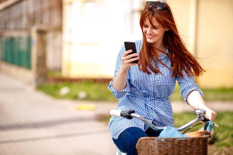 Junges Mädchen, das Smartphone mit Reitfahrrad in der Stadt verwendet stockbilder