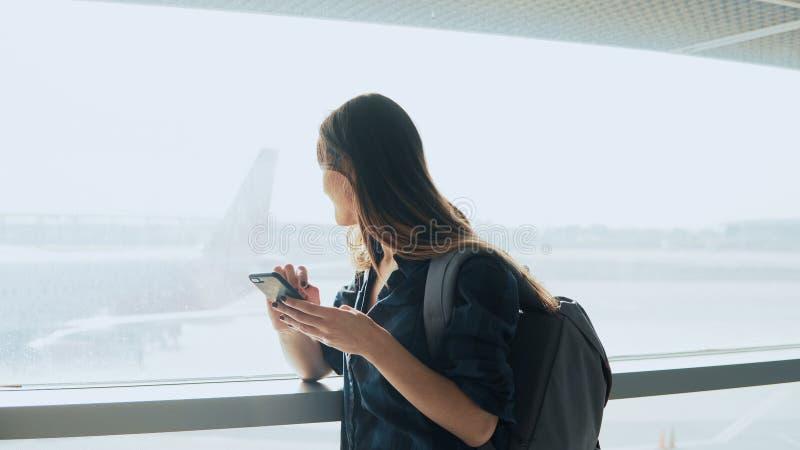 Junges Mädchen, das Smartphone nahe Flughafenfenster verwendet Glückliche europäische Frau mit Rucksack verwendet bewegliche APP  lizenzfreie stockbilder