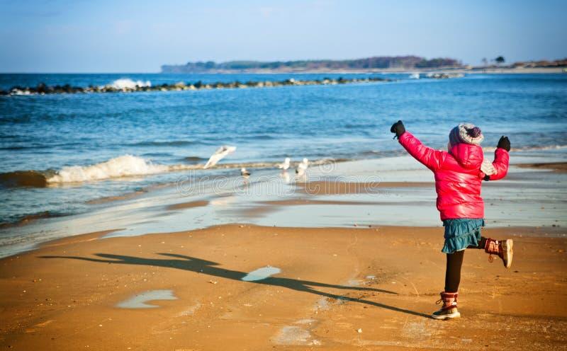 Junges Mädchen, das Spaß auf Winter Ostsee-Strand hat stockfotografie