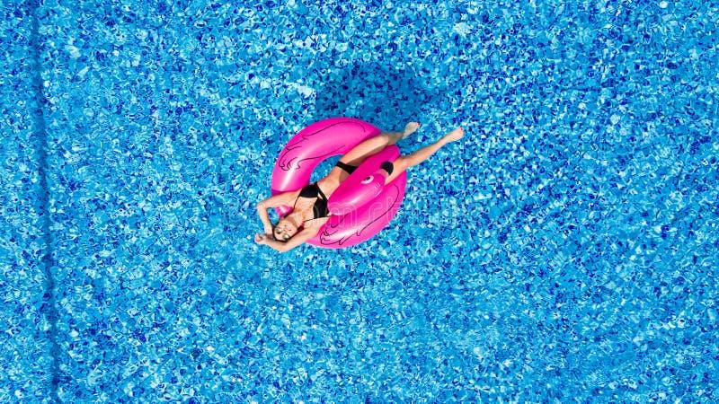 Junges Mädchen, das Spaß hat und Spaß im Pool auf einem aufblasbaren rosa Flamingo in einem Badeanzug im Sommer vom abov lacht un lizenzfreie stockfotografie