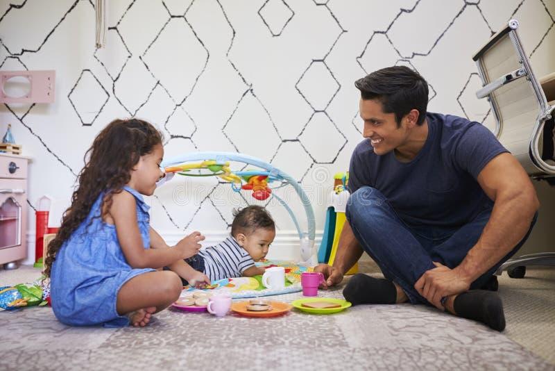 Junges Mädchen, das Teeparty mit dem Vati, sitzend auf dem Boden, Babybruder auf einer Spielmatte neben ihnen spielt stockfotografie