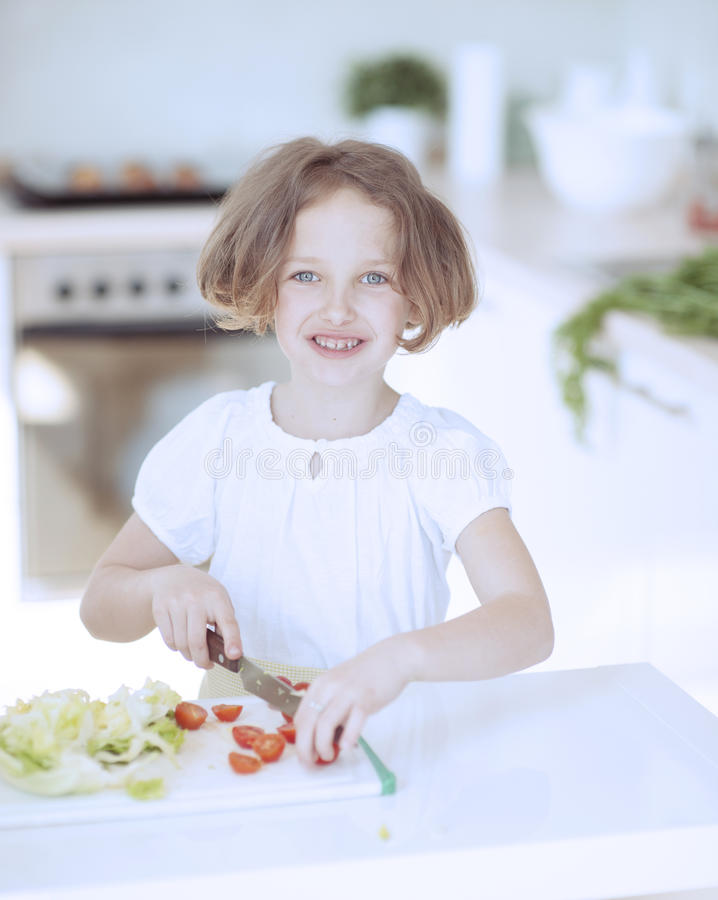 Junges Mädchen, das Tomaten hackt und einen Salat in der Küche macht stockfoto