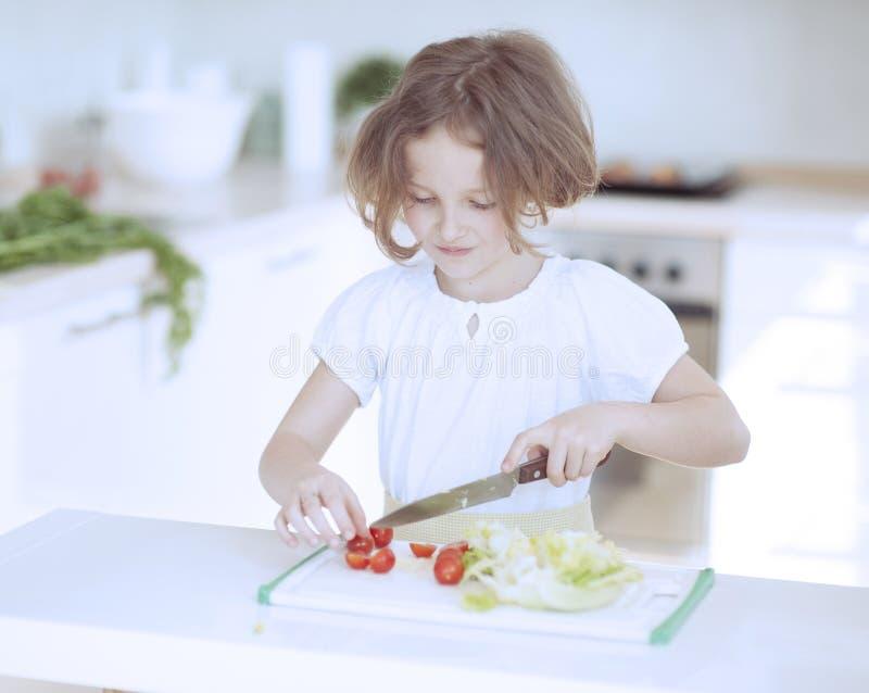 Junges Mädchen, das Tomaten hackt und einen Salat in der Küche macht stockbilder