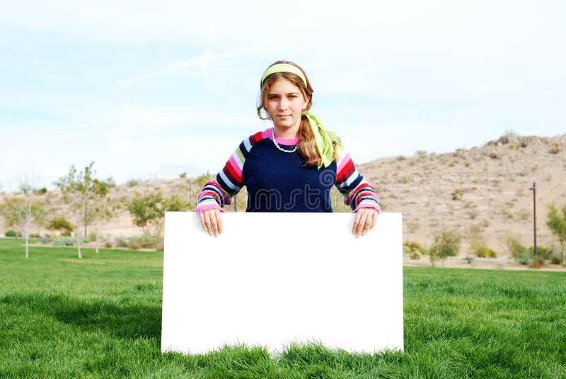 Junges Mädchen, das unbelegtes Zeichen anhält stockfotos