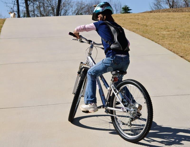 Junges Mädchen, das versucht, herauf einen Hügel radzufahren stockbilder