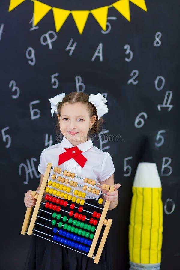 Junges Mädchen, das vor Tafelbacksteinmauer mit Buchstaben auf ihr tragende Schuluniform mit enormer pensil Gelbfarbe steht stockfoto