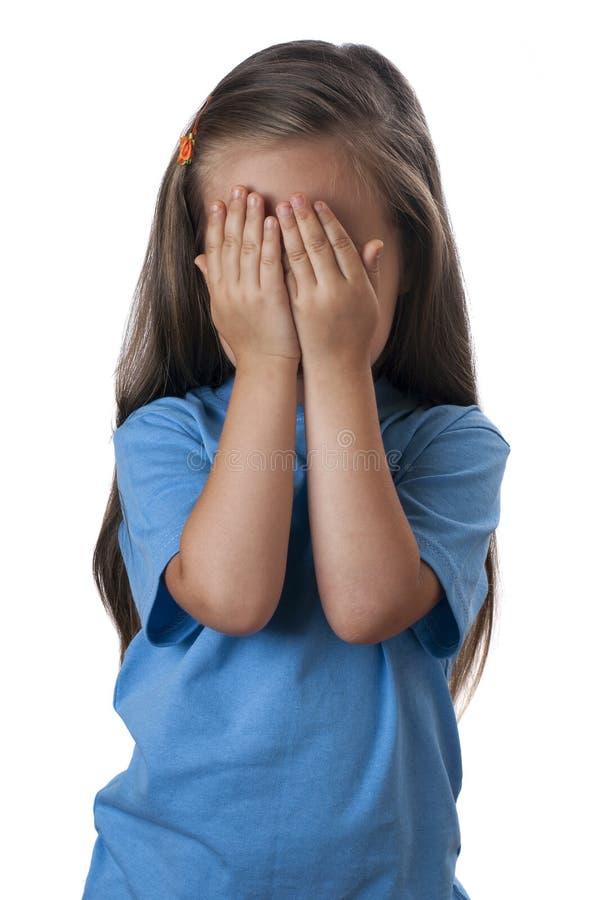 Junges Mädchen, das vorbei ihr Gesicht bedeckt stockfotografie