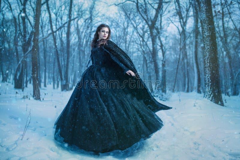 Junges Mädchen, das in Winterwald geht lizenzfreie stockfotos