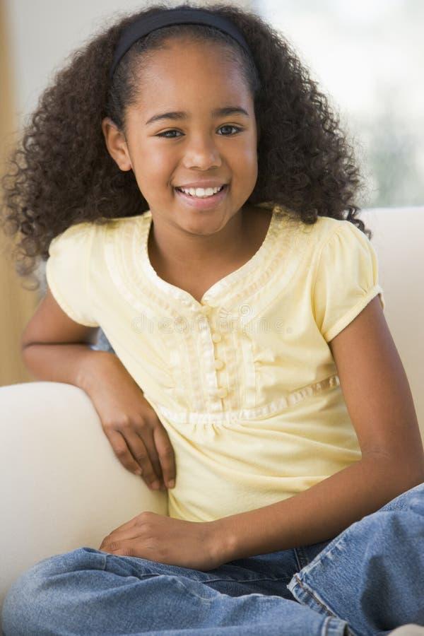 Junges Mädchen, das zu Hause auf einem Sofa sitzt stockfotos