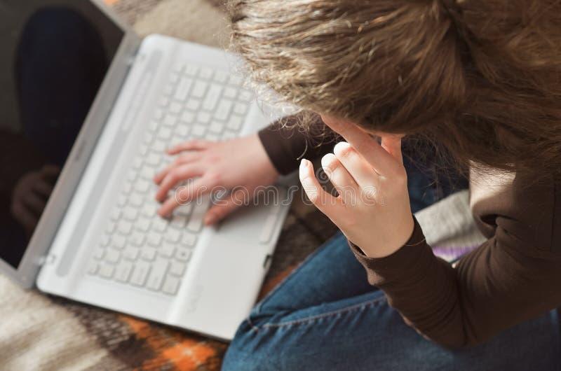 Junges Mädchen, das zu Hause für einen Laptop studiert lizenzfreies stockfoto