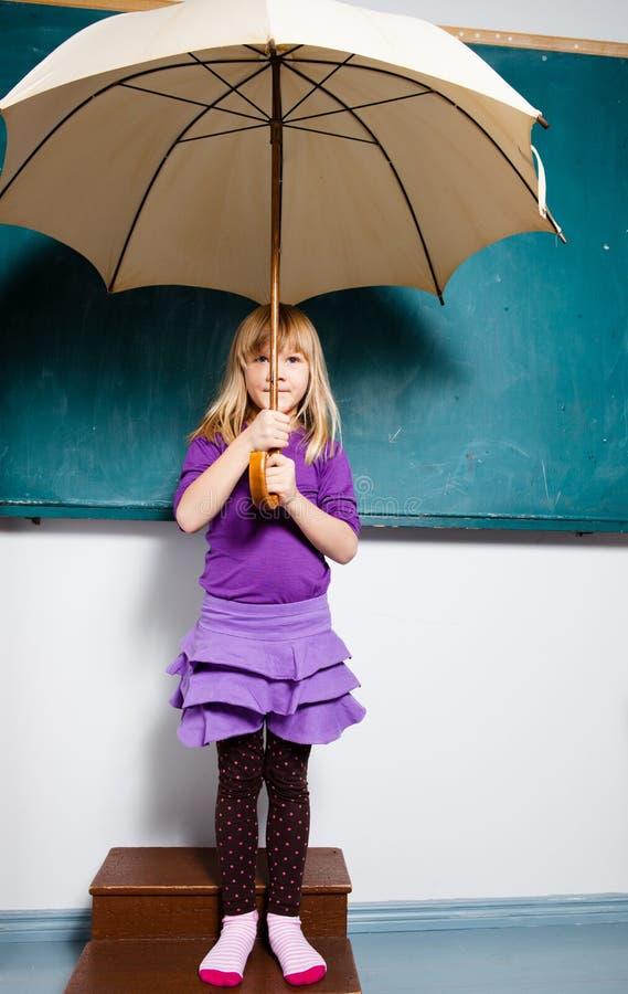 Junges Mädchen, das zuhause Regenschirm anhält lizenzfreies stockbild