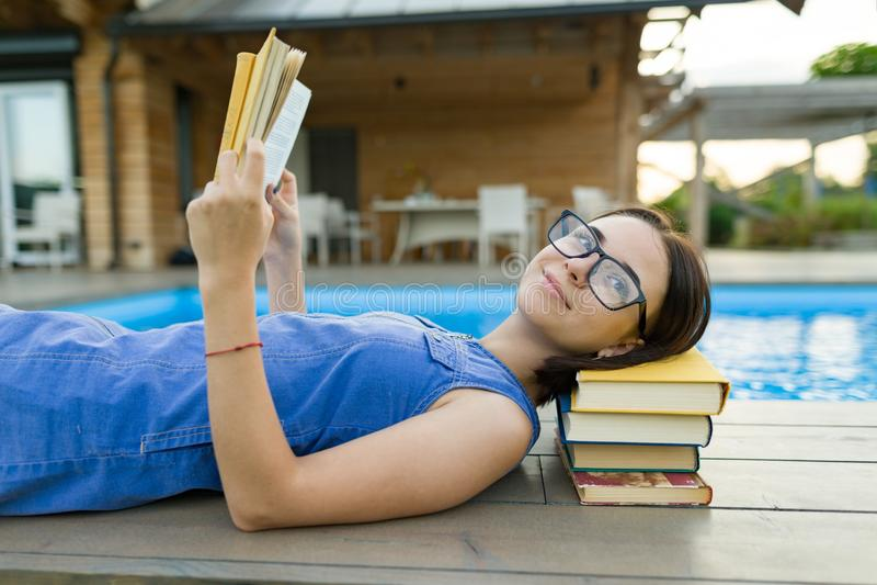 Junges Mädchen in den Gläsern nahe dem Pool mit einem Stapel von Büchern, Lesebuch Bildung, Sommer, Wissen lizenzfreie stockfotografie