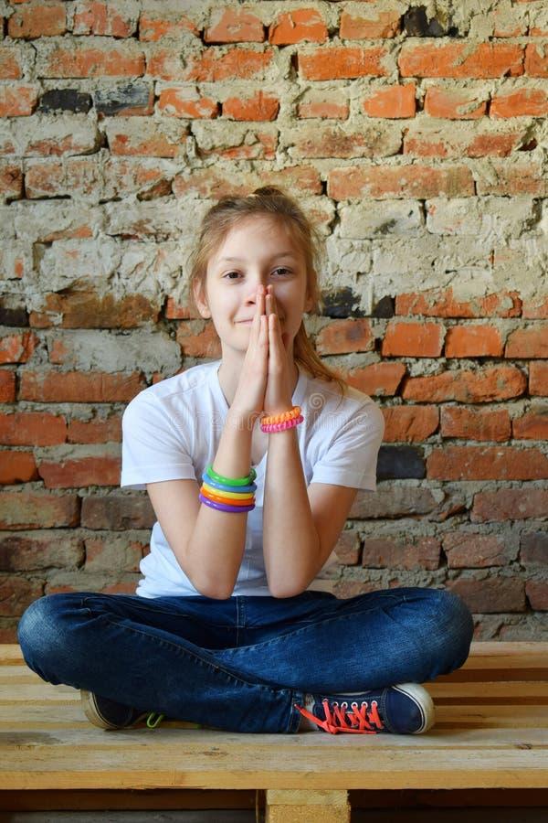 Junges M?dchen in den Jeans und im wei?en T-Shirt sitzt auf dem Boden und betet Konzeptportr?t eines angenehmen freundlichen gl?c stockfotos