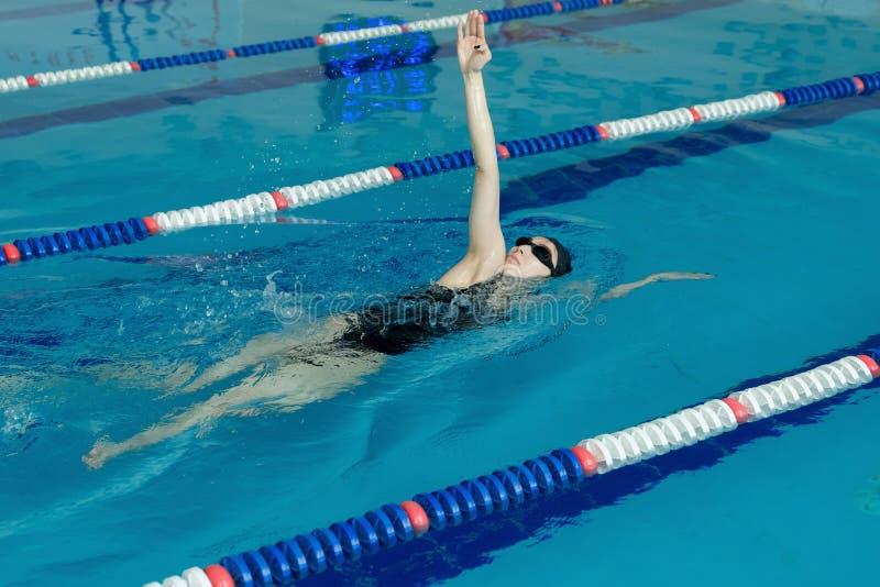 Junges Mädchen in den Schutzbrillen und Kappe, die hintere Schleichenanschlagart im Pool des blauen Wassers schwimmen stockfoto