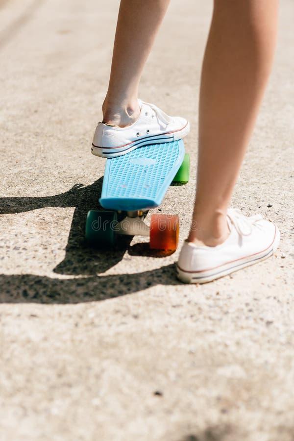 Junges Mädchen in den Turnschuhen auf Skateboard stockbild