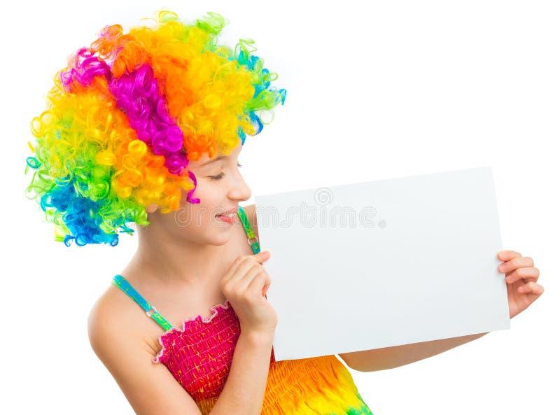 Junges Mädchen in der Clownperücke mit weißem Blatt Papier lizenzfreies stockbild