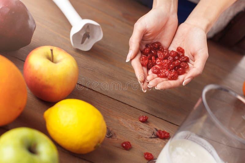 Junges Mädchen an der gesunden Lebensstilstellung der Küche, die Kirschen für Smoothienahaufnahme hält lizenzfreies stockbild