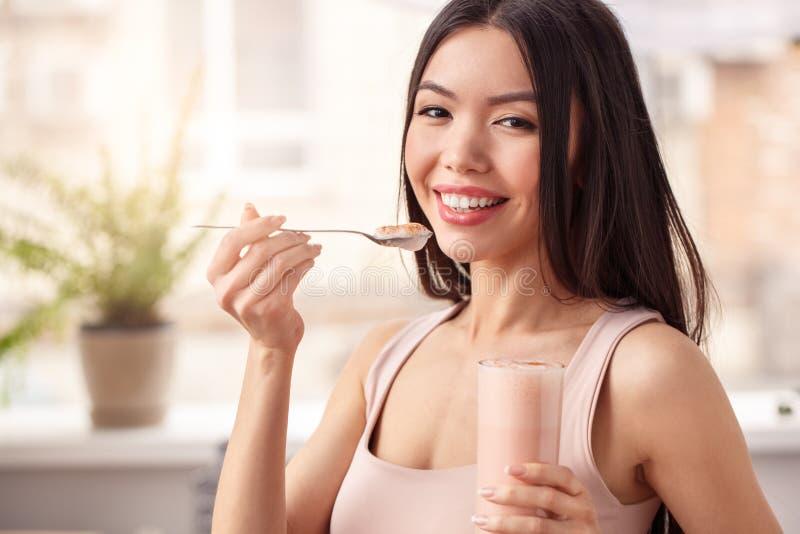 Junges Mädchen an der gesunden Lebensstilstellung der Küche Smoothie von der schauenden Glaskamera essend glücklich lizenzfreie stockbilder
