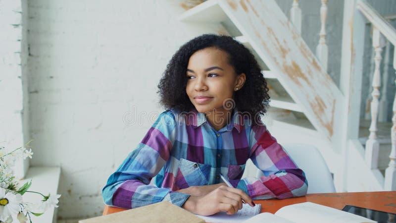 Junges Mädchen der jugendlichen gelockten behaarten Mischrasse, das an der Tabellenkonzentration fokussiert sitzt, Lektionen für  stockfotografie