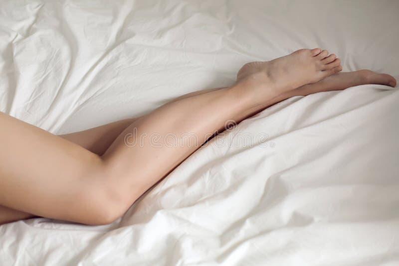 Junges Mädchen der nackten weiblichen Beine, das in einem weißen Bett liegt stockfoto