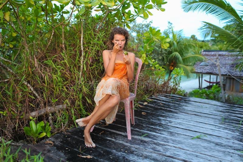 Junges Mädchen des Fotos, das tropische Früchte im Dschungelhaus genießt Lächelnde Frau, die Sommer der Kühlzeit im Freien verbri lizenzfreies stockbild