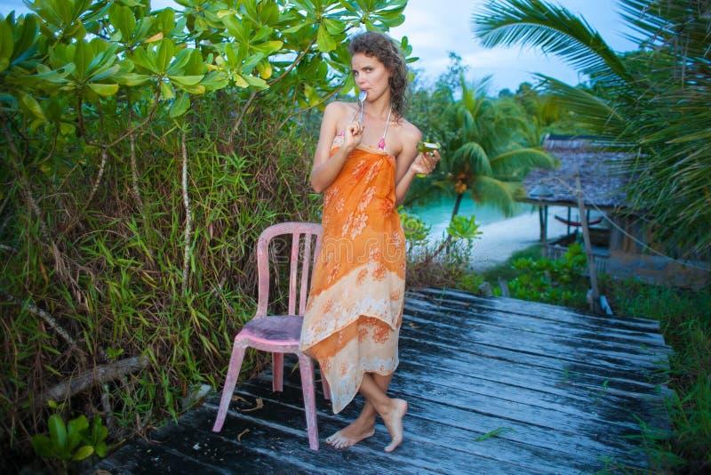 Junges Mädchen des Fotos, das tropische Früchte im Dschungelhaus genießt Lächelnde Frau, die Sommer der Kühlzeit im Freien verbri lizenzfreies stockfoto