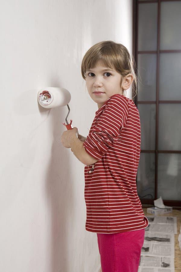Junges Mädchen des glücklichen lustigen Lächelns mit Malerpinsel. stockfotografie