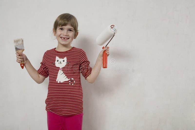 Junges Mädchen des lustigen Lächelns mit Malerpinsel. stockbild