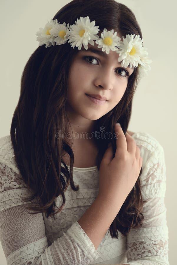 Junges Mädchen des Porträts mit Blumen im Haar lizenzfreie stockbilder
