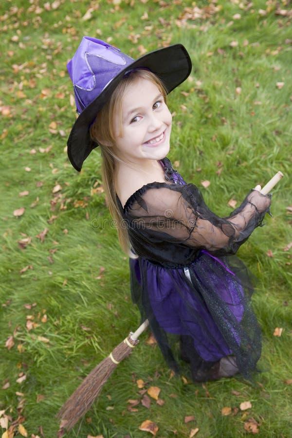 Junges Mädchen draußen im Hexekostüm auf Halloween stockfotografie