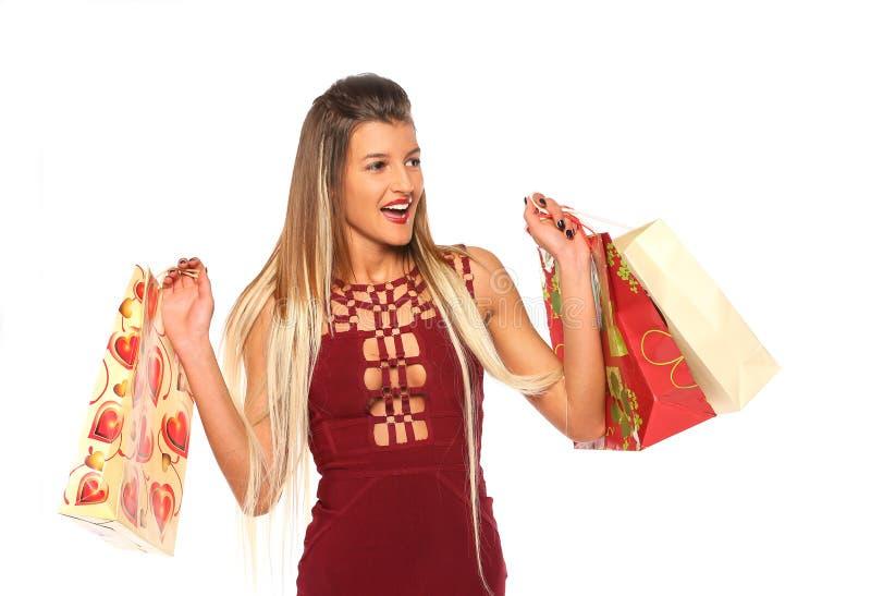 Junges Mädchen in einem Burgunder-Kleid hält Einkaufstaschen lizenzfreie stockbilder