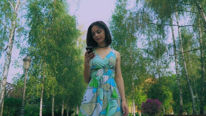 Junges Mädchen in einem hellen Kleid ist im Park und liest eine Mitteilung auf Ihrem Telefon und Lächeln lizenzfreie stockfotografie