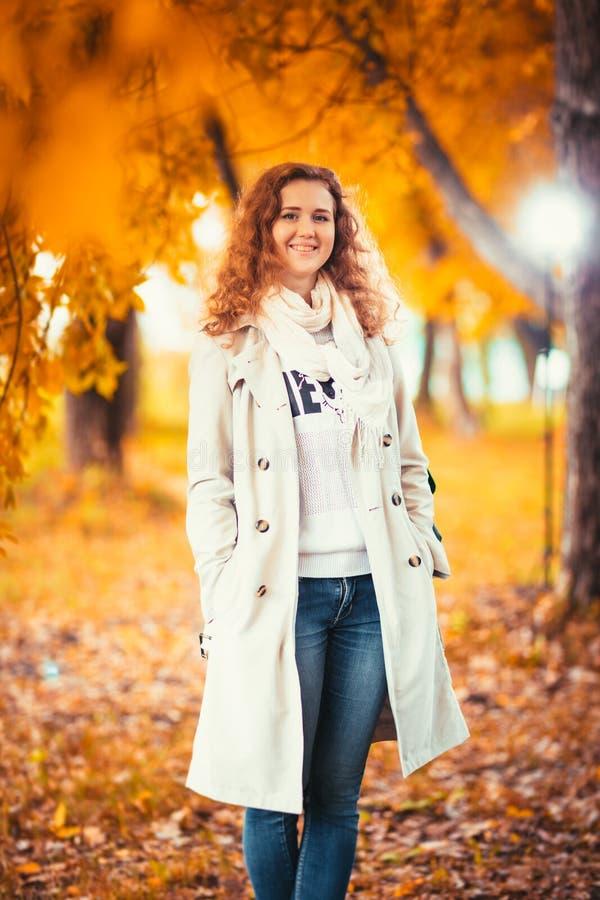 Junges Mädchen in einem hellen Mantel auf dem Hintergrund des Herbstparks stockfotografie