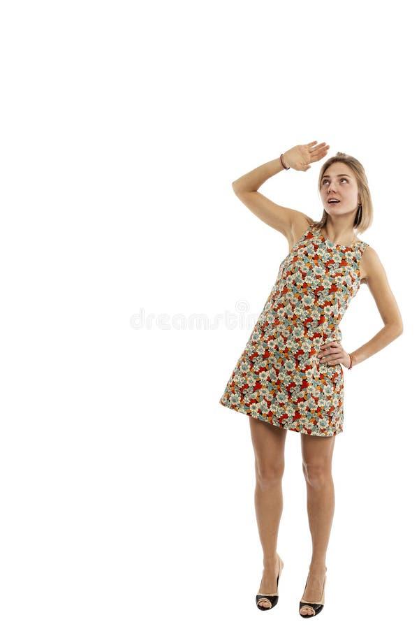 Junges Mädchen in einem kurzen Kleid im vollen Wachstum schaut oben, wird lokalisiert auf einem weißen Hintergrund stockfotografie