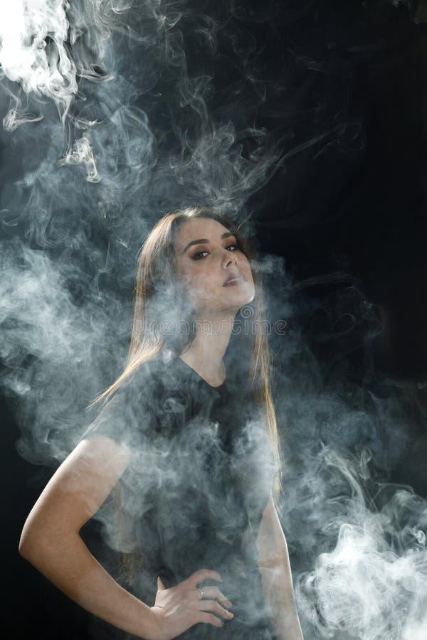 Junges Mädchen in einem schwarzen T-Shirt, das eine elektronische Zigarette vaping ist auf einem schwarzen Hintergrund raucht stockfoto