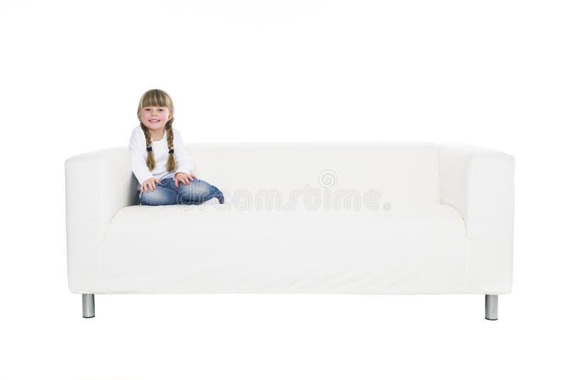 Junges Mädchen in einem Sofa stockfotos