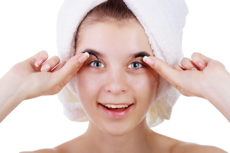 Junges Mädchen in einem Tuch nachdem eine Dusche mit den Klammern, versuchend auf Wimpern lizenzfreie stockfotos