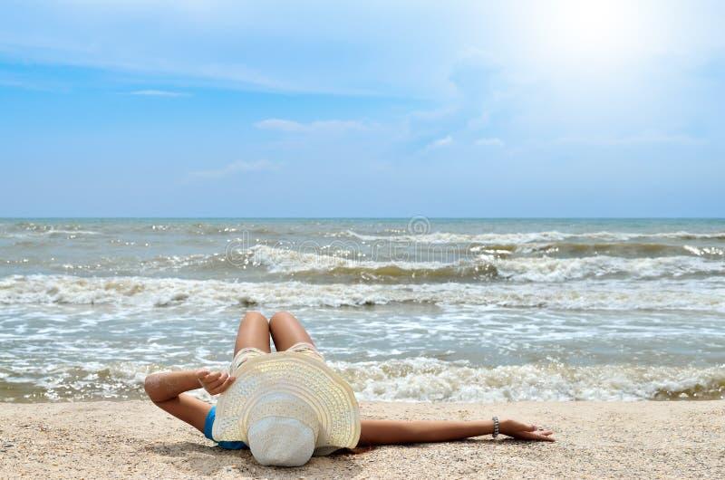 Junges Mädchen in einem weißen Hut auf dem Seestrand Sauberer, sandiger Strand gegen das blaue Meer stockfotos