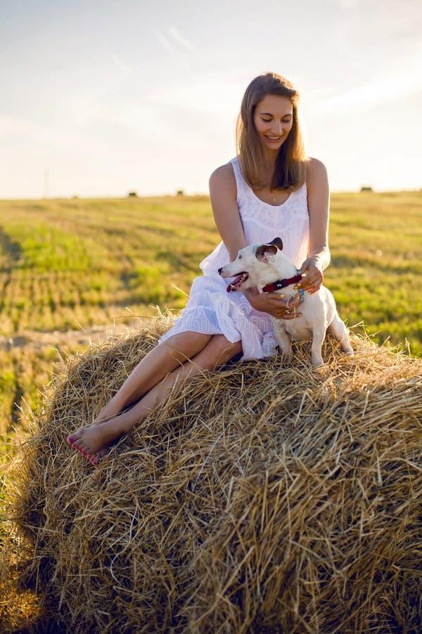 Junges Mädchen in einem weißen Kleid sitzt mit Jack Russell Terrier-Hund auf dem Heuschober stockfotos