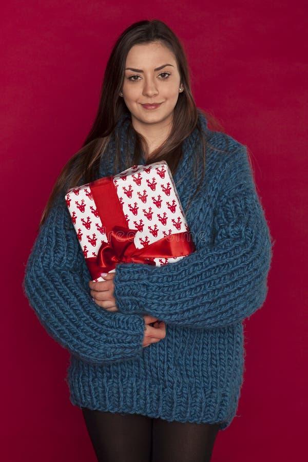 Junges Mädchen in einer blauen Strickjacke drückt ein Weihnachtsgeschenk zusammen lizenzfreie stockfotos
