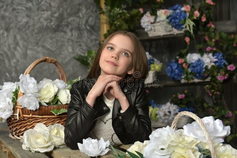 Junges Mädchen in einer schwarzen Lederjacke mit Blumen stockfotos