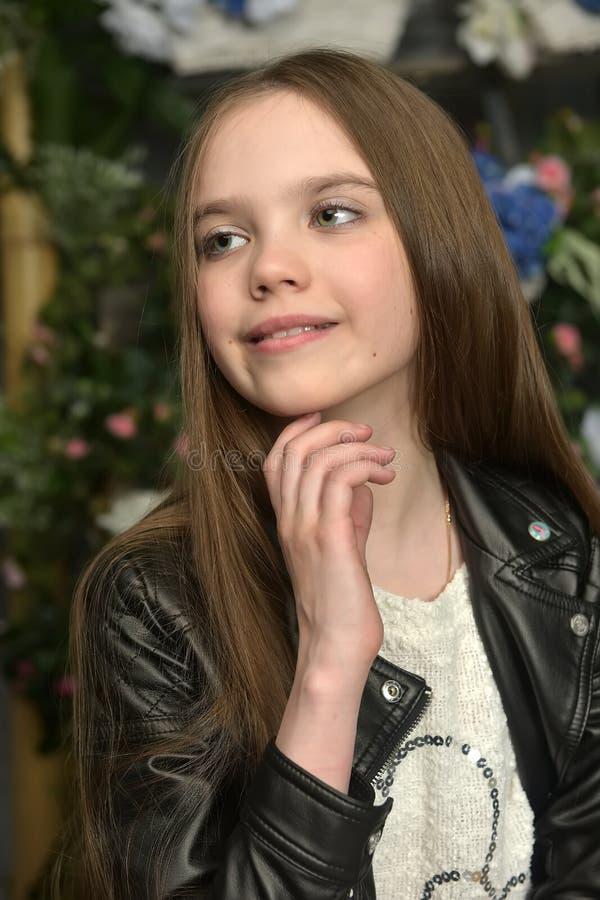 Junges Mädchen in einer schwarzen Lederjacke mit Blumen stockbild