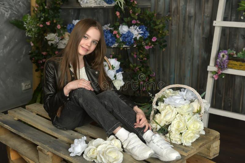 Junges Mädchen in einer schwarzen Lederjacke mit Blumen lizenzfreies stockbild