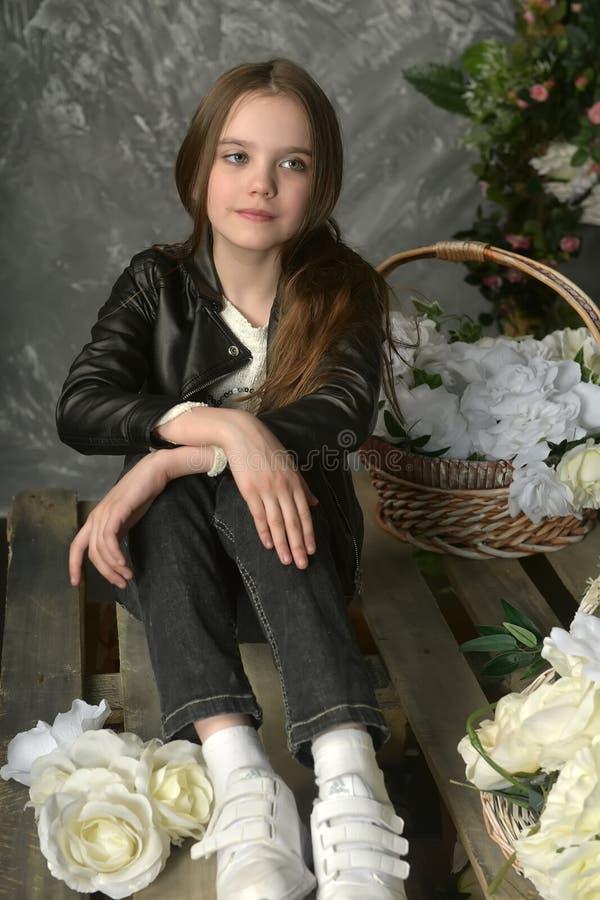 Junges Mädchen in einer schwarzen Lederjacke mit Blumen stockfoto