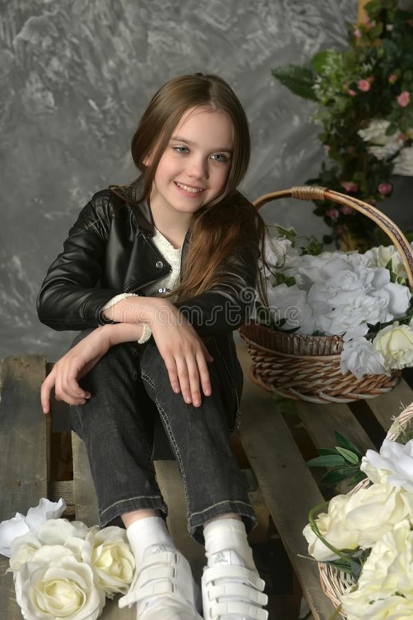 Junges Mädchen in einer schwarzen Lederjacke mit Blumen stockfotografie