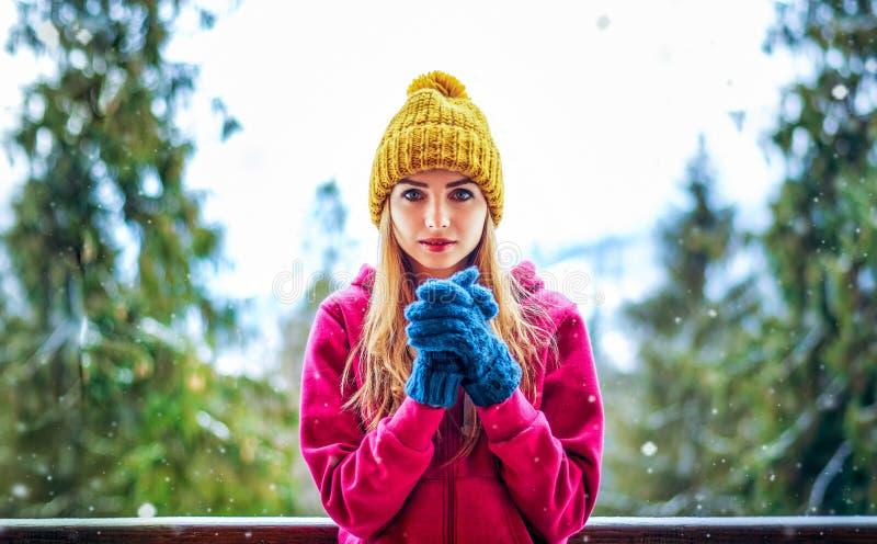 Junges Mädchen in einer Strickmütze und in Handschuhen, die unter dem Schneien stehen stockfoto
